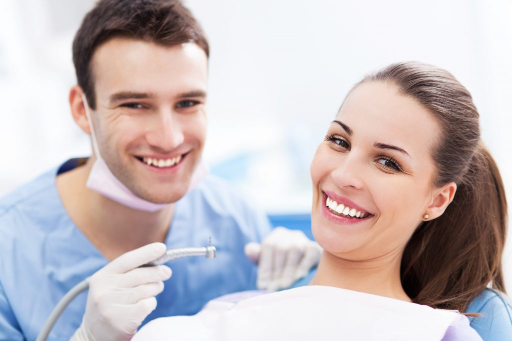 dentist and his patient are smiling