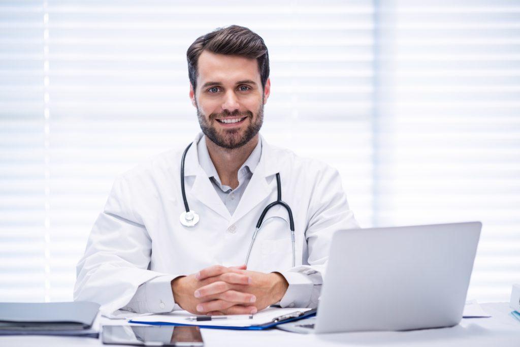 Portrait of male doctor sitting at desk