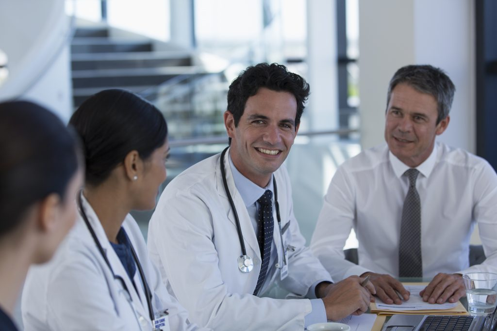 Portrait confident doctors talking in hospital meeting