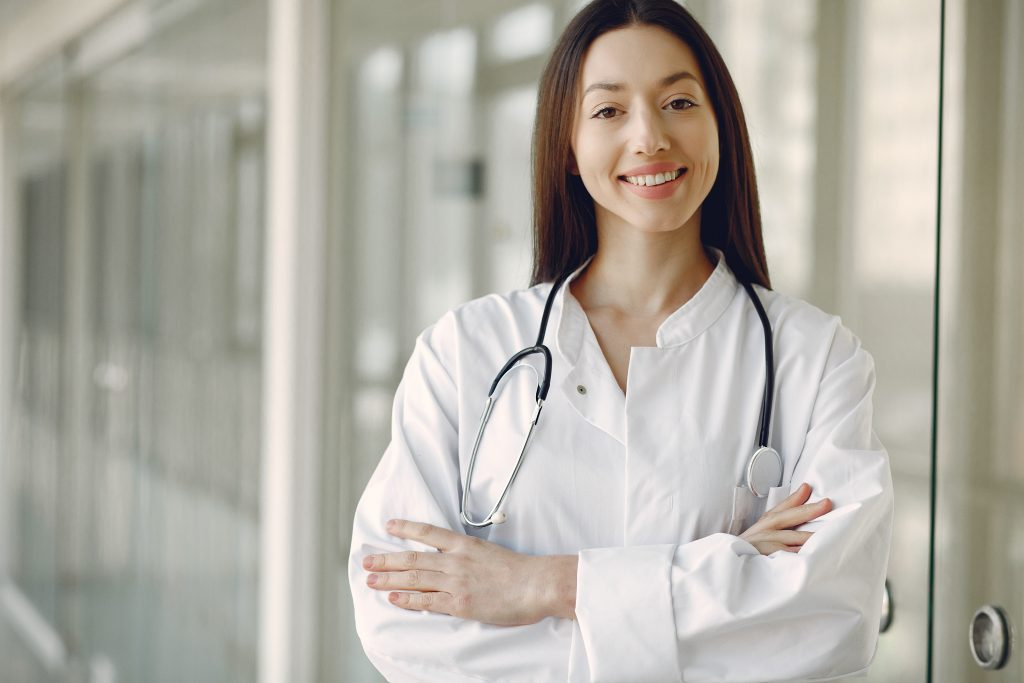 Woman doctor in a white uniforn standing in a hall