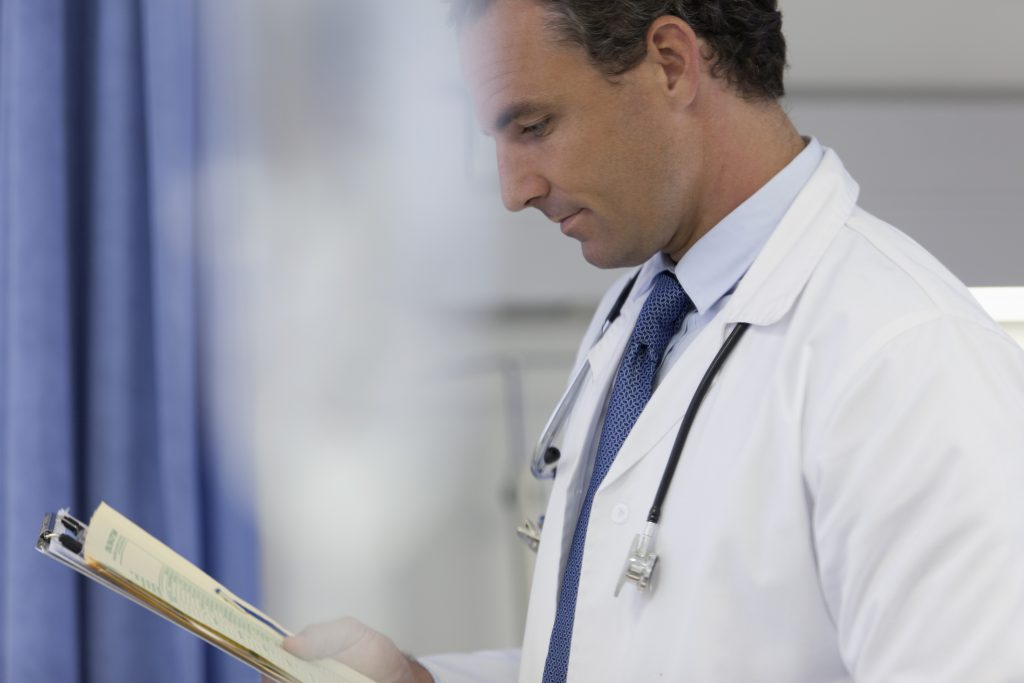 Male doctor with medical record making rounds in hospital