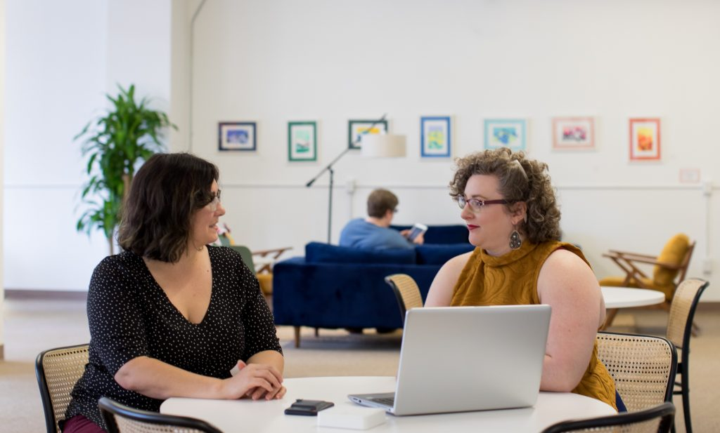 two size plus women sitting in front of the computer