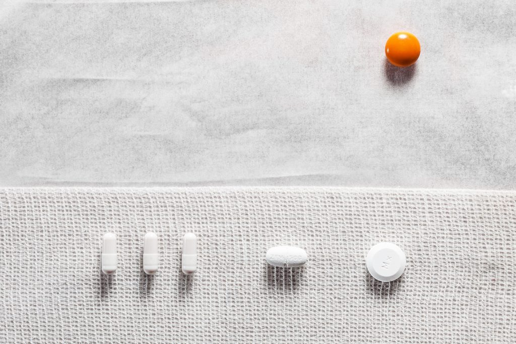 High angle shot of orange and white medicine tablets on white surface