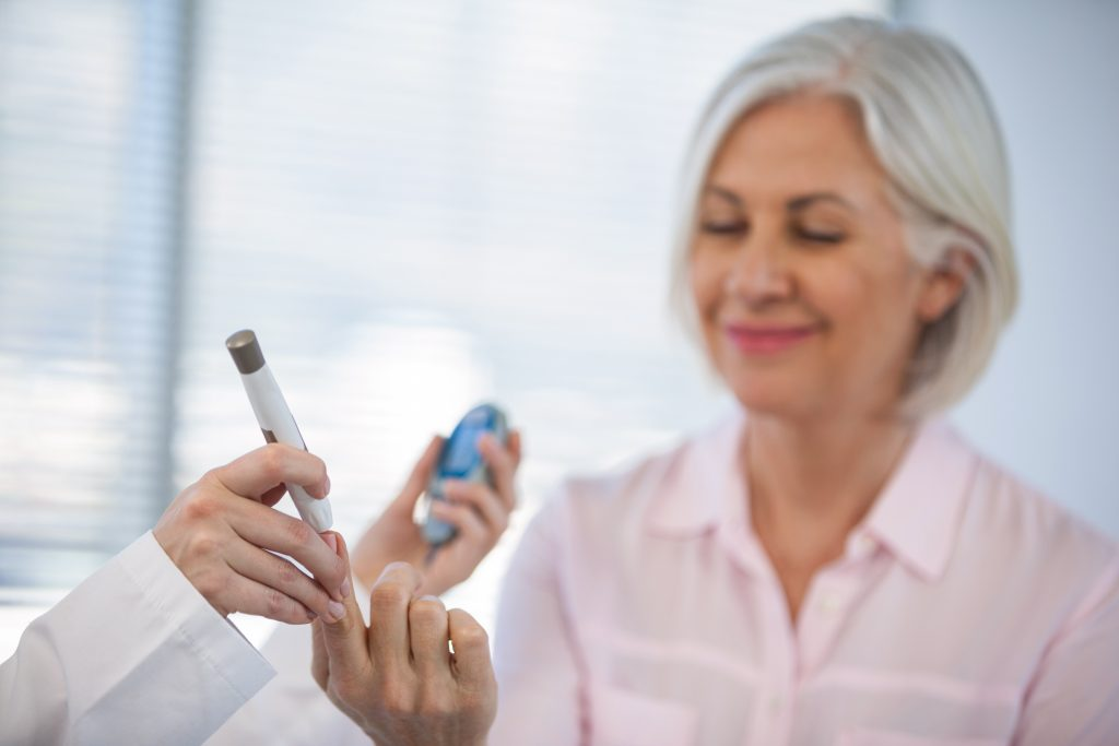 Doctor checking glucose level in diabetic patient