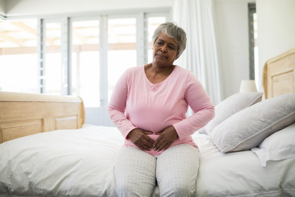 Senior woman having a huge stomach pain in bedroom