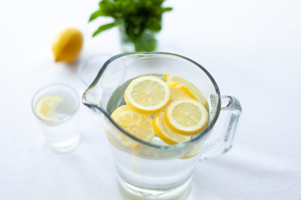 water with lemon on white table